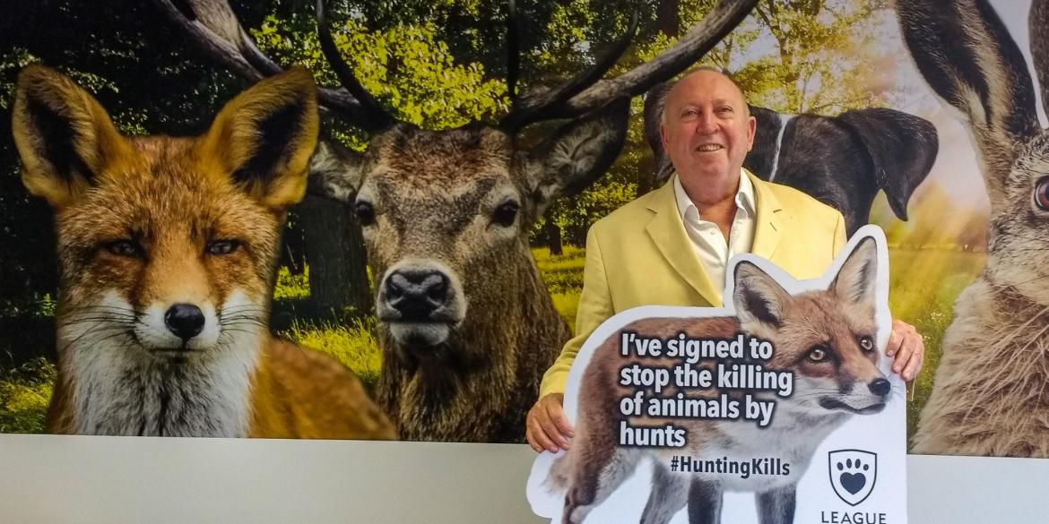 Keith Taylor MEP holds a fox shape sign pledging: I've signed the petition to stop the killing of animals by hunts
